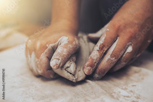 Obraz na plátně Female potter works with clay, craftsman hands close up