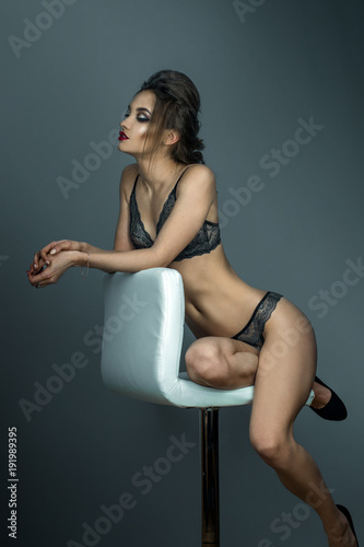 Fotografia  adorable woman with red lips and beautiful hairstyle sits on white leather chair