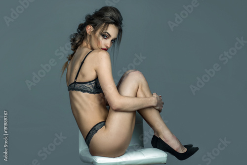 Stampa su Tela  beauty lady with red lips and beautiful hairstyle sits on white leather chair in