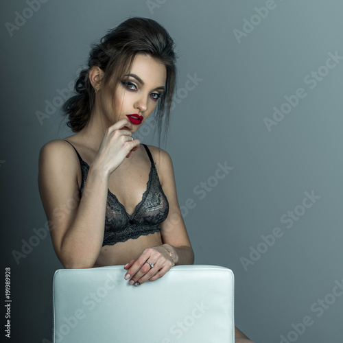 Fotografia  portrait of gorgeous woman with red lips and beautiful hairstyle sits on white l