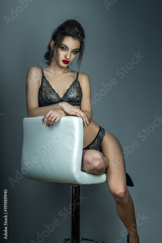 Fotografia  gorgeous woman with red lips and beautiful hairstyle sits on white leather chair
