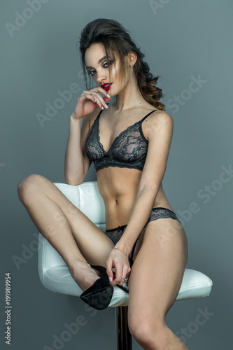 Stampa su Tela  sexual lady with red lips and beautiful hairstyle sits on white leather chair in