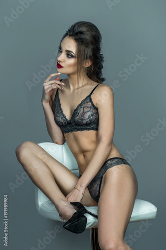 Stampa su Tela  attractive lady with red lips and beautiful hairstyle sits on white leather chai
