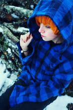 Adolescente En La Nieve En Un Día De Invierno Sobre Unos Troncos De Leña