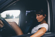 Pretty brunette woman poses inside a car.
