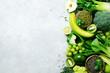 Leinwandbild Motiv Organic green vegetables and fruits on grey background. Copy space, flat lay, top view. Green apple, zucchini, cucumber, avocado, kale, lime, kiwi, grapes, banana, broccoli, marbled lentils, mung bean