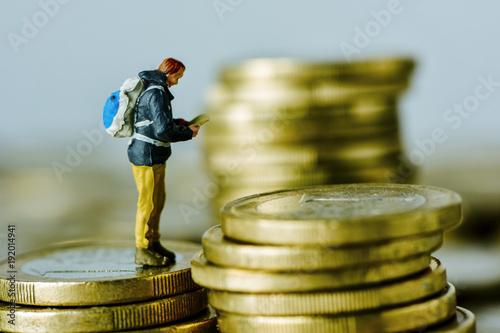 Photo miniature traveler on a pile of euro coins