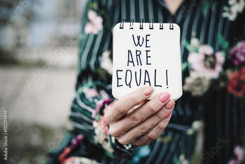 Fotografía  woman shows notepad with the text we are equal