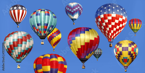 Panorama of Hot Air Balloons Acending in a Bright Blue Sky