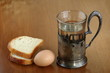 Faceted glass of hot water for tea in an ancient silver cup holder, one egg and two slices of bread