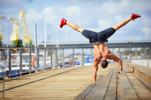 Fotografia  Athletic man doing a handstand exercise during an outdoors workout in the city