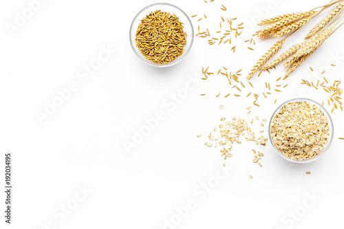 Foto Oatmeal and oat in bowls near sprigs of wheat on white background top view copy