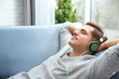 Relaxed young man listening to music at home