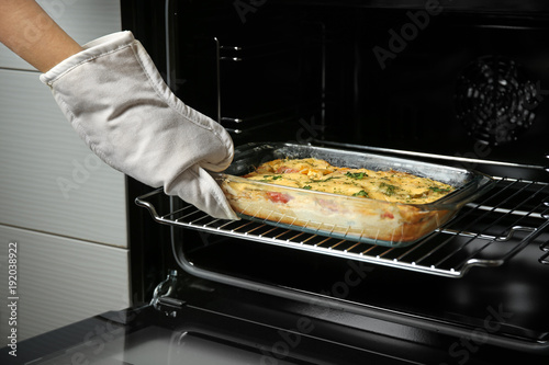 Foto auf AluDibond Gericht bereit Woman taking glass baking dish with delicious casserole from oven, closeup