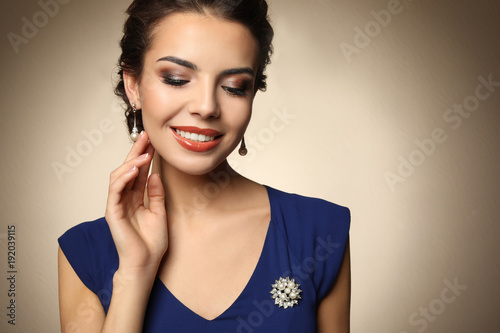 Beautiful young woman with elegant jewelry on color background Fototapeta