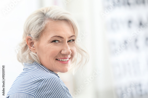 Mature woman with hearing aid indoors Fototapet