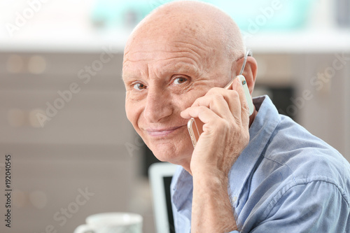 Valokuva  Hearing impaired man talking on phone at home