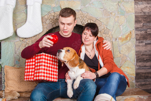Deurstickers Ontspanning Young family playing with pretty beagle dog near fireplace