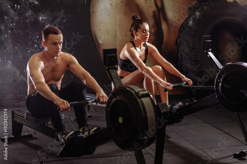Autocollant pour porte Fitness Two sportsmen sitting on rowing machines and working out in light spacious gym