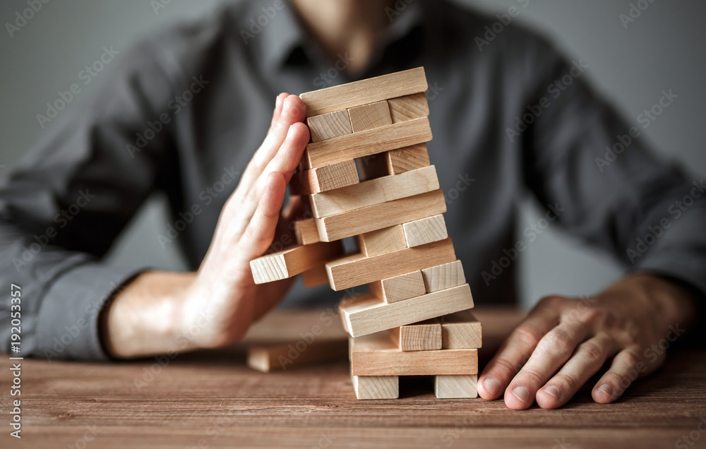 Fototapeta Businessman holds the model of business, made from wood blocks. Alternative risk concept, business plan and business strategy. Insurance concept.