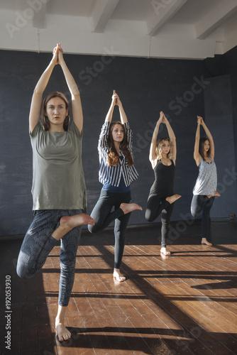 Deurstickers School de yoga Caucasian women standing on one leg in yoga class