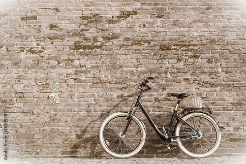 Black retro vintage bicycle with old brick wall.