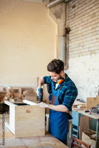 Fototapeta Wood boring drill in hand drilling hole in wooden bar obraz na płótnie