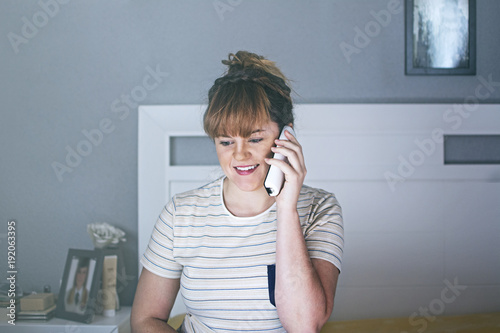 chica joven hablando por télefono en su habitación