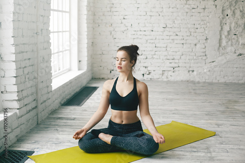 Atractive young Caucasian woman working out at home, doing yoga exercise on green mat, sitting in lotus pose with legs folded and eyes closed, meditating, breathing deeply, relaxing body and mind