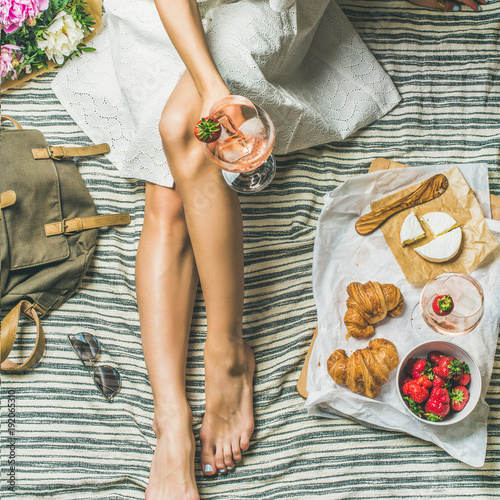 Keuken foto achterwand French style romantic picnic setting. Woman in dress with glass of wine, strawberries, croissants, brie cheese, sunglasses, peony flowers on blanket, top view, square crop. Outdoor gathering concept