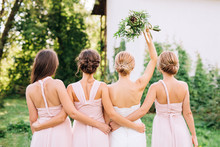 Bride Standing With Her Back  And Raised Hand With A Bouquet  In The Embraces Of Three Bridesmaids In Pink Dresses Transformer