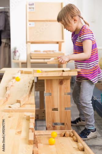 Fototapeta girl playing with wooden puzzles. obraz na płótnie