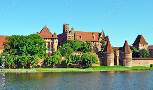 Fototapety, obrazy: Ancient European knight's castle, which is located in Poland, the city of Malbork. Fortress close-up on the lake surrounded by greenery. tourist center with ancient architecture.