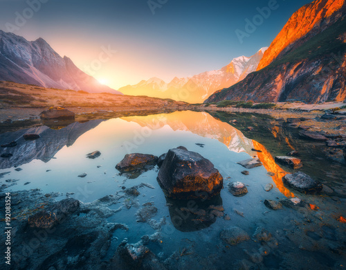 Beautiful landscape with high mountains with illuminated peaks, stones in mountain lake, reflection, blue sky and yellow sunlight in sunrise. Nepal. Amazing scene with Himalayan mountains. Himalayas