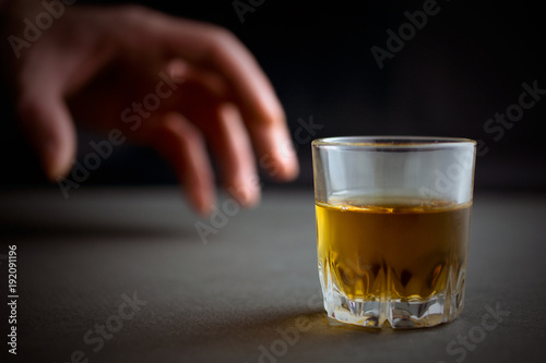 Poster Bar hand reaches for a glass of whiskey or cognac or alcohol drink, alcoholism and alcohol abuse concept, defocused, selective focus, close up, gray table, dark background