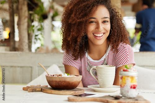 Plakat Dobra, kędzierzawa kobieta o radosnym wyglądzie i kędzierzawych włosach pije kawę z deserem na tarasie, ma szczęśliwy wyraz twarzy, lubi spędzać wolny czas i odpoczywać samotnie. Ludzie, wolny czas i styl życia.
