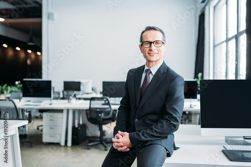 Photo  smiling businessman in eyeglasses sitting on table in office