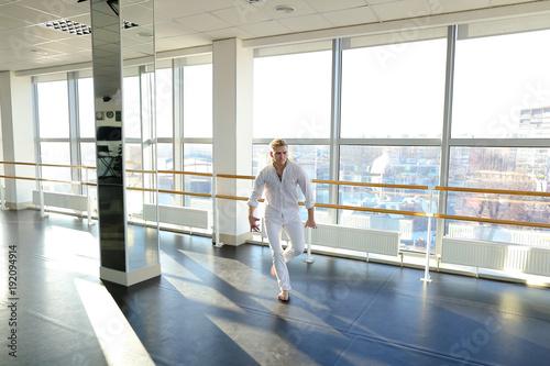 Fotografía  Male person dancing in tectonic way near window
