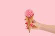 Leinwandbild Motiv Hand holding strawberry ice cream cone on white background