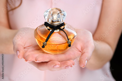 Fototapeta cropped shot of woman holding bottle of perfume obraz