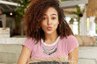 Curly African American female rounds lips at camera, flirts with handsome man at restaurant, feels relaxed on comfortable sofa, wears striped t shirt and round earrings. Facial expressions concept