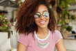 Beautiful smiling African American teen girl has fun during free time at cafeteria, waits for order, happy to speak with friends, wears sunglasses, has curly bushy hairdo. Female student rests indoor