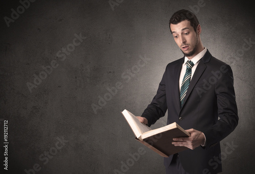 Fotografering  Businessman holding a book.