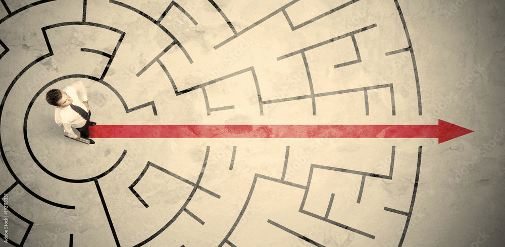 Fototapeta Business person standing in the middle of a circular maze