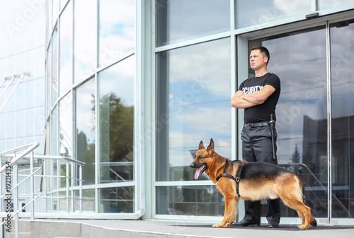 Fotografía  Security guard with dog near building
