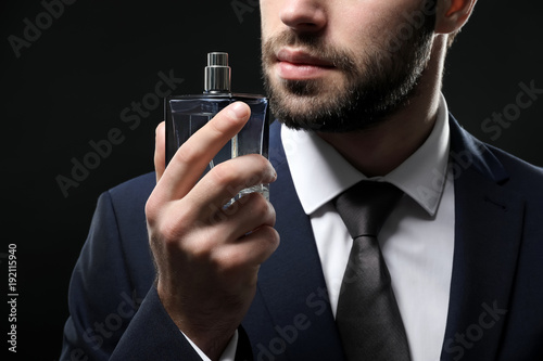 Fotografie, Obraz  Handsome man in formal suit and with bottle of perfume on dark background, close
