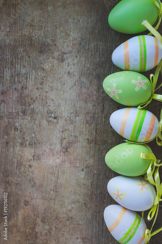 Top view of green, orange and white easter eggs decorations on old rustic, vintage wooden background, vintage toned Wallpaper Mural