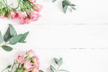 Flowers Composition. Frame Made Of Eucalyptus Branches And Pink Rose Flowers On White Wooden Background. Flat Lay, Top View, Copy Space