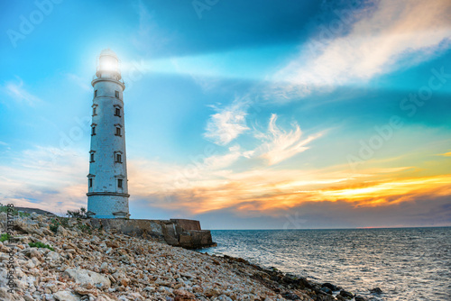 Foto auf Gartenposter Port Lighthouse searchlight beam through sea air at night. Seascape at sunset