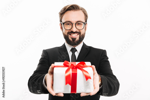 Fototapeta Handsome businessman gives you a gift present box. obraz
